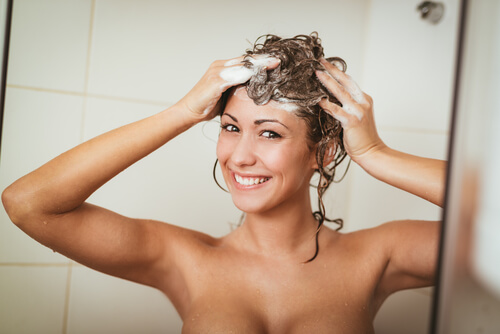 A smiling woman washing her hair