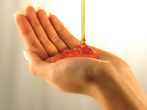 A woman pouring Art Naturals Hair Growth Shampoo into her hand