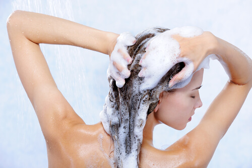 A woman washing her hair with OGX Fight Fallout Plus shampoo