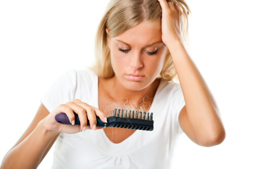 A young, blonde woman looking at her comb and worrying about balding