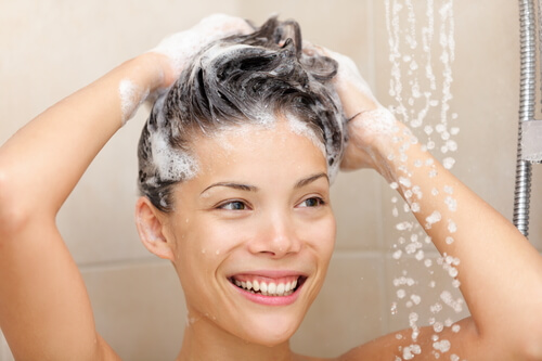 A woman smiling as she shampoos her hair