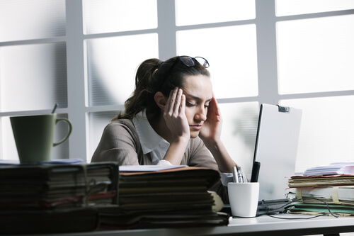 A stressed woman sitting at a desk and holding her head