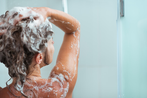 A woman applying shampoo in the shower