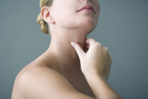 A female performing a self examination of her thyroid