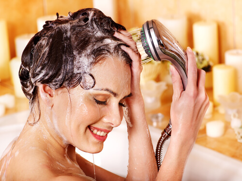 A woman rinsing shampoo from her hair