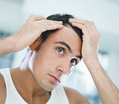 A man checking out his receding hairline