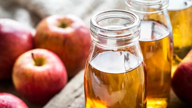 Bottles of apple cider vinegar next to apples